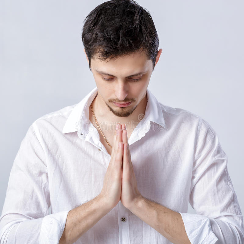 Portrait of attractive man with dark hair in white shirt in yoga stock images
