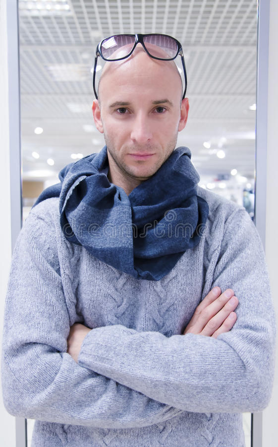 Portrait of attractive man in grey knitted sweater. And blue scarf stock photos