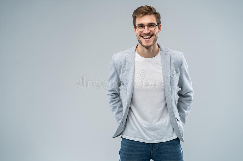 Portrait of attractive masculine fashionable modern stylish guy wearing blue blazer, jeans keeping hands in pockets. Isolated on gray background stock photos