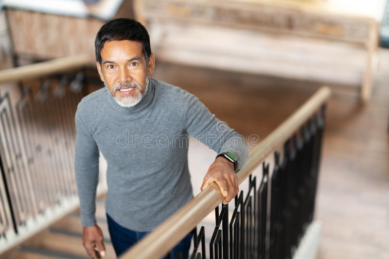 Portrait of attractive mature asian man retired with stylish short beard smiling and walking up stairs holding handrail in coffee. Shop. Old happy handsome royalty free stock photo