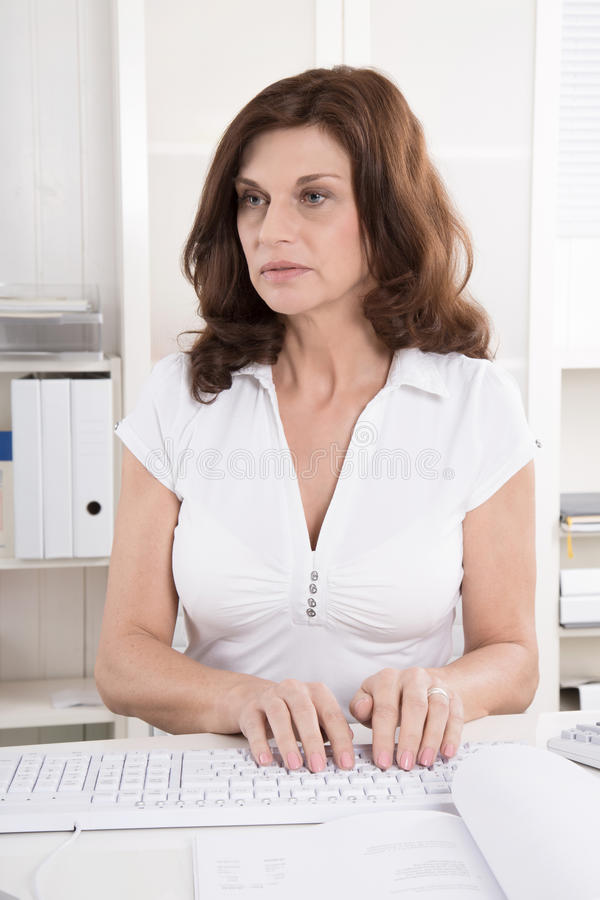Portrait: Attractive middle aged woman writing on computer. stock photos