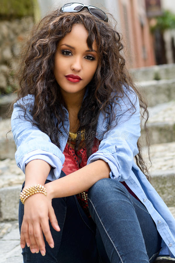 Attractive mixed woman in urban background wearing stock photography