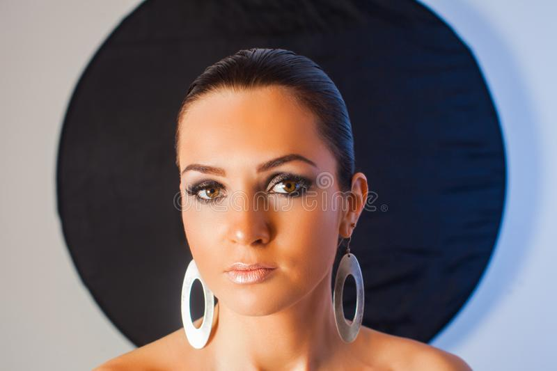 Portrait of makeup model with large earrings royalty free stock photography