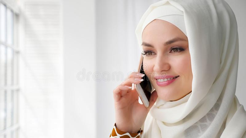 Attractive muslim woman in hijab is talking mobile phone. royalty free stock photography