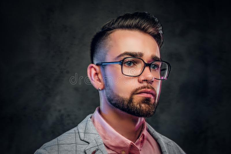 Portrait of attractive pensive man in checkered blazer, pink shirt and glasses.  royalty free stock images