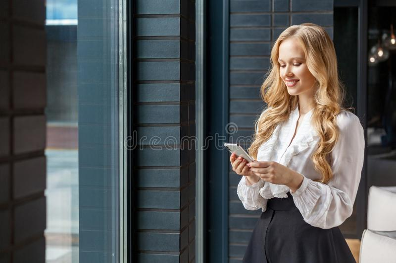 Portrait of attractive positive businesswoman smiling happily while using cellphone. standing near window, indoors royalty free stock images