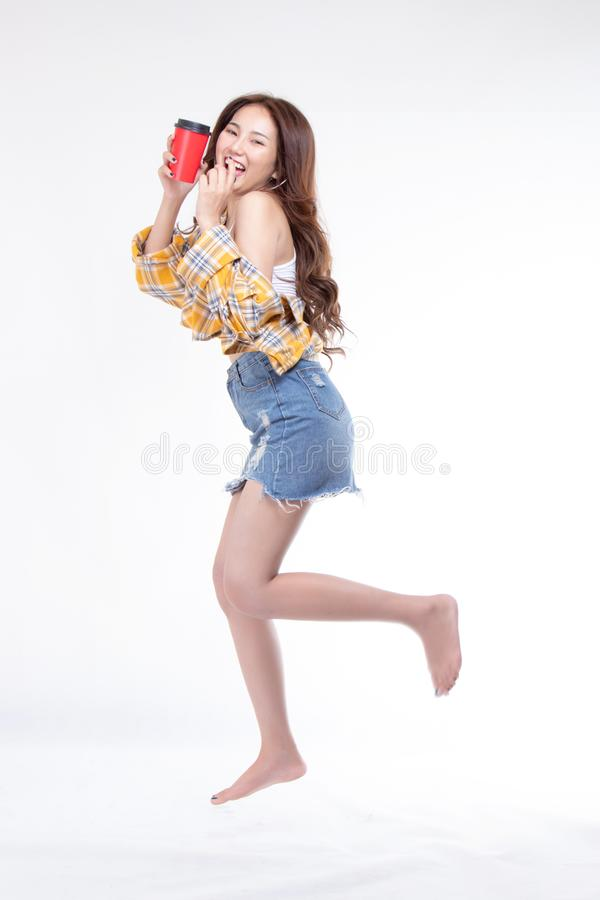 Portrait of attractive pretty lovely stylish nice cute cheerful a young asian woman wearing yellow shirt hand holding red coffee royalty free stock photos
