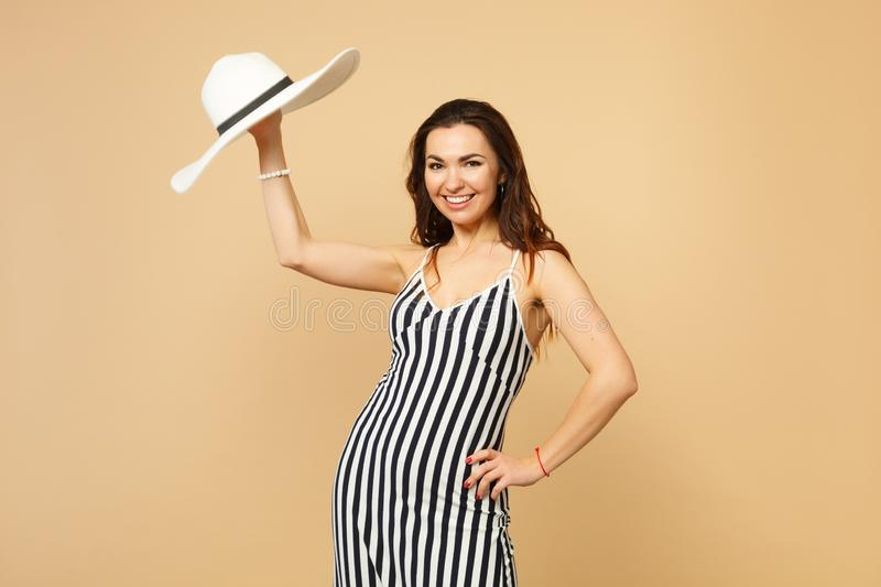 Portrait of attractive pretty young woman in black and white striped dress hold hat, looking camera isolated on pastel royalty free stock photo