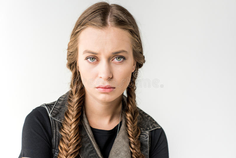 Portrait of attractive rocker girl with braids looking at camera isolated royalty free stock photography