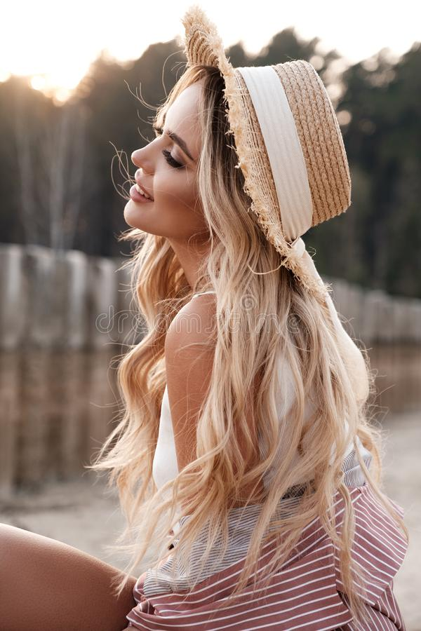 Portrait of an attractive, romantic and c adorable provincial girl with long loose hair in a straw hat. Sunset, soft sunny colors. stock photos