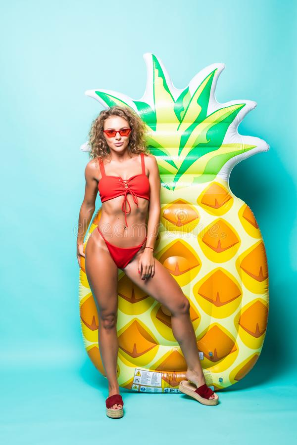 Portrait of attractive slim body woman in red bikini and sunglasses posing with pineapple inflatable mattress isolated on gre. Portrait of attractive woman in royalty free stock photos