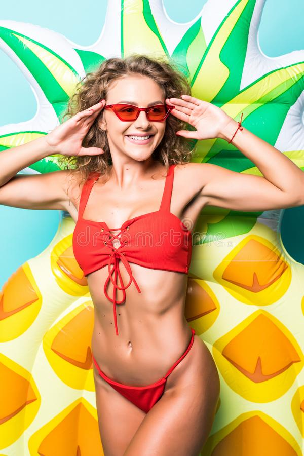 Portrait of attractive slim body woman in red bikini and sunglasses posing with pineapple inflatable mattress isolated on gre. Portrait of attractive woman in stock images