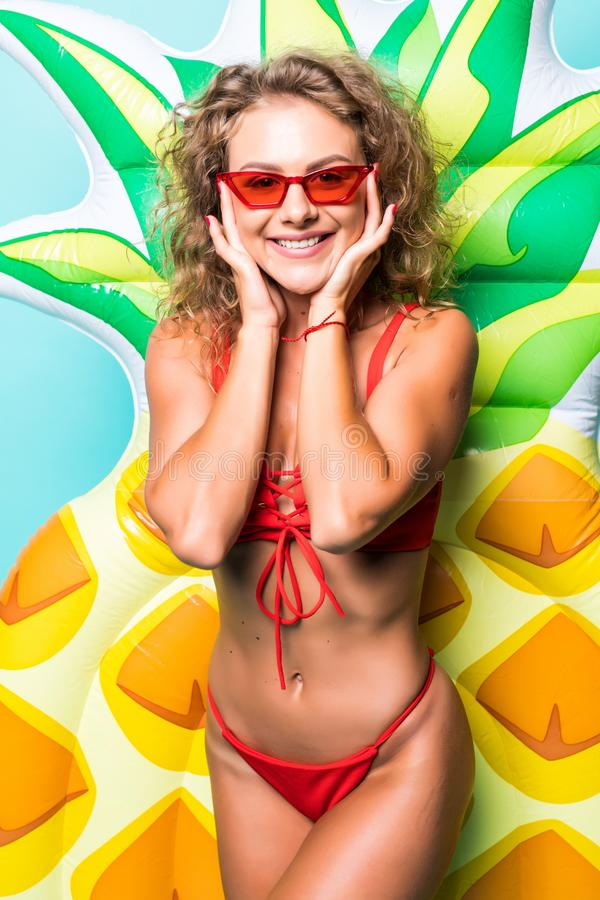 Portrait of attractive slim body woman in red bikini and sunglasses posing with pineapple inflatable mattress isolated on gre. Portrait of attractive woman in stock photo