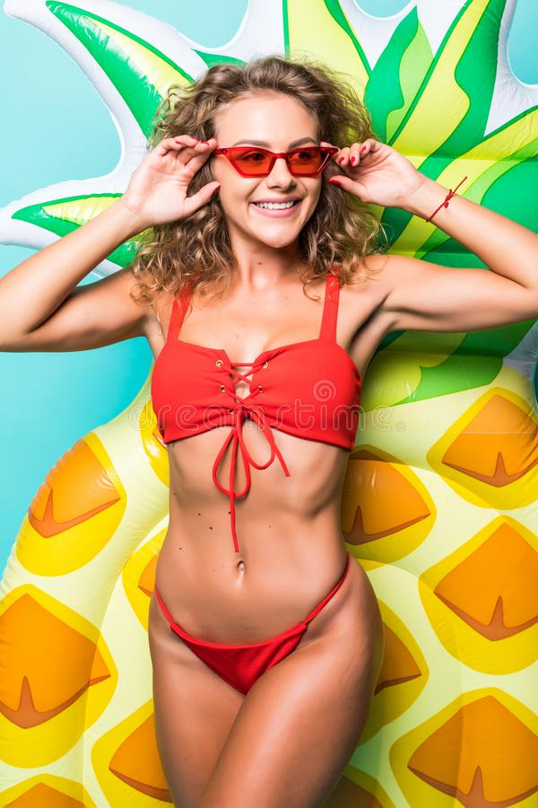Portrait of attractive slim body woman in red bikini and sunglasses posing with pineapple inflatable mattress isolated on gre. Portrait of attractive woman in stock image