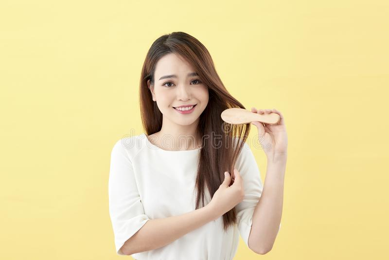 Portrait of attractive smiling woman brushing her hair isolated on yellow studio shot.  stock photos