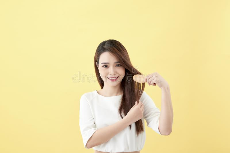 Portrait of attractive smiling woman brushing her hair isolated on yellow studio shot.  stock photo