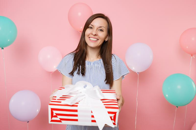 Portrait of attractive smiling young woman in blue dress holding red box with gift present on pastel pink background royalty free stock photos