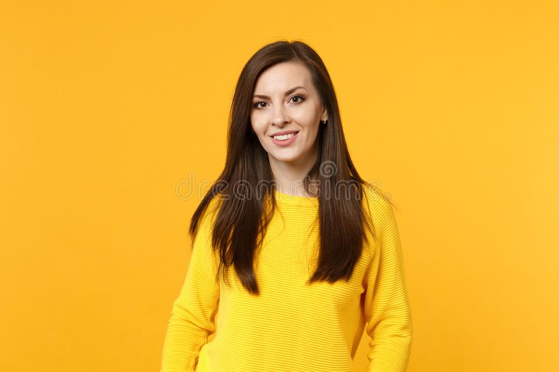 Portrait of attractive smiling young woman in casual clothes looking camera isolated on bright yellow orange wall royalty free stock images