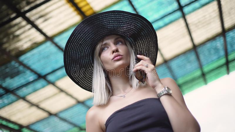 Portrait of an attractive smiling young woman in a hat. Stylish fashionably dressed royalty free stock photo