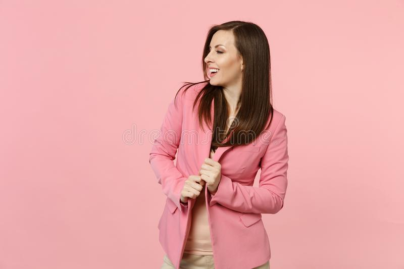 Portrait of attractive smiling young woman holding hands on jacket looking aside  on pastel pink wall background stock photo