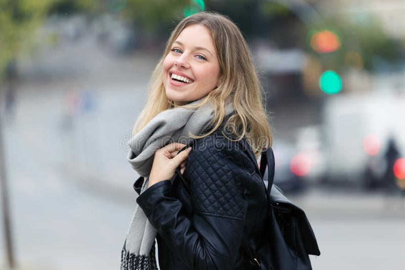 Attractive smiling young woman looking at the camera in the street. Portrait of attractive smiling young woman looking at the camera in the street stock photos