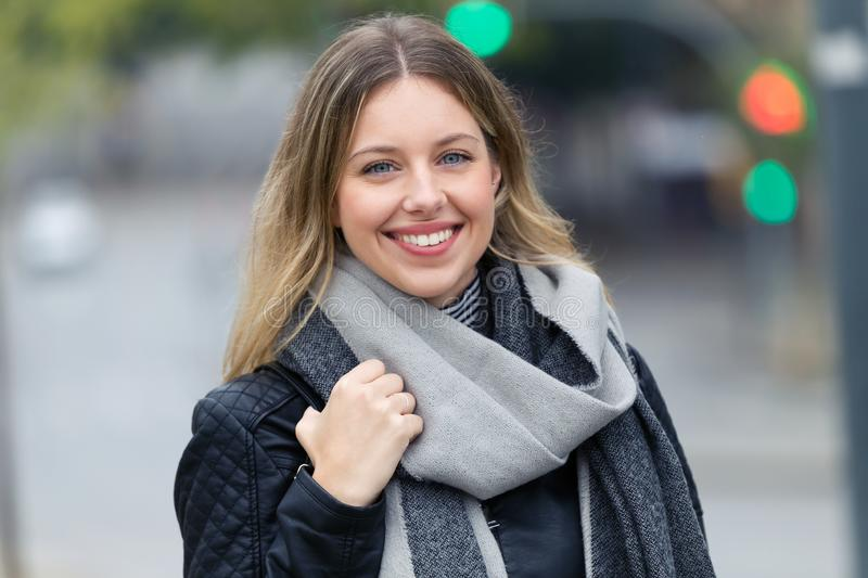 Attractive smiling young woman looking at the camera in the street. Portrait of attractive smiling young woman looking at the camera in the street royalty free stock photography