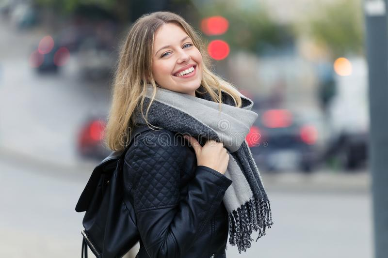 Attractive smiling young woman looking at the camera in the street. Portrait of attractive smiling young woman looking at the camera in the street stock images