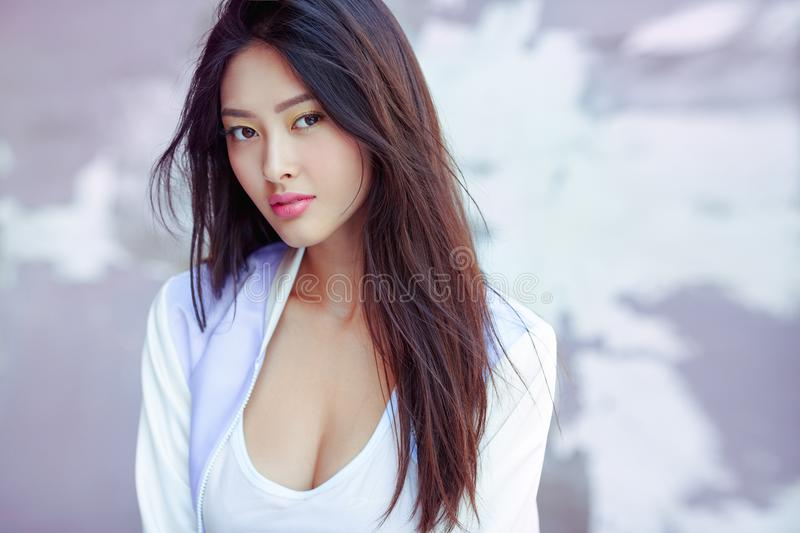 Asian fashion model outdoors. Portrait of attractive sporty asian woman with elegant hairstyle and perfect soft colorful makeup. Skin care cosmetics concept stock photos