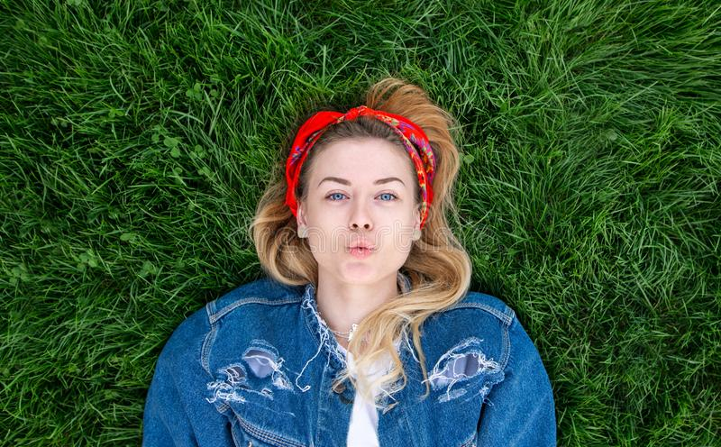 Portrait of an attractive stylish girl in a denim jacket lying on a green lawn and posing on the camera royalty free stock photos