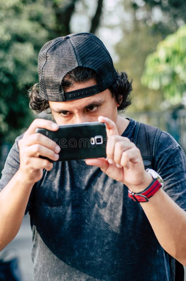 Portrait of an attractive teen boy holding his smartphone with his hand and take photograph. Use the technology of outdoor smartphones to take pictures stock image