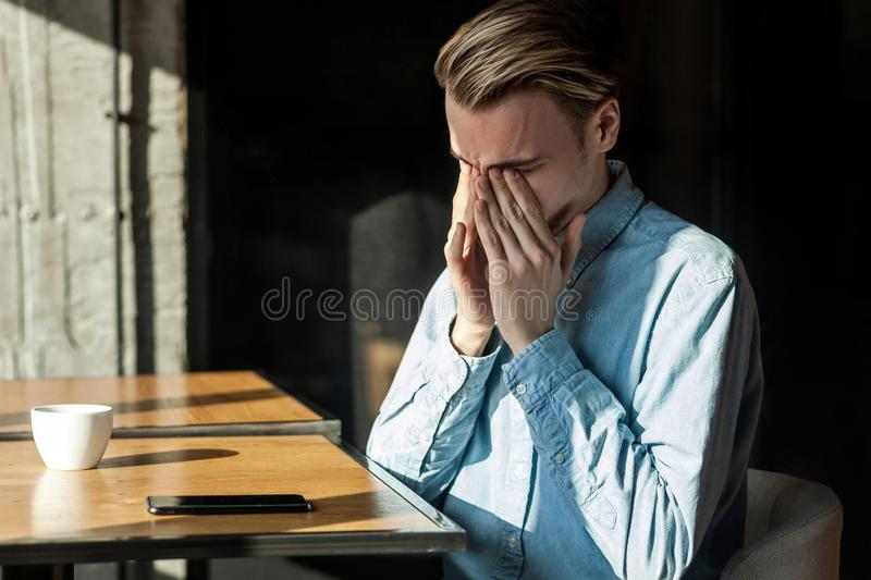Portrait of attractive tired unhappy young bearded man in denim blue shirt sitting in cafe and covering eyes with finger after royalty free stock photos