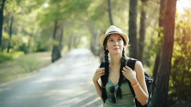 Portrait of Attractive tourist girl smiling and looking into camera while walking and hiking beautiful forest royalty free stock photography