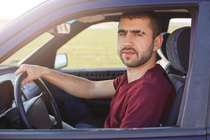 Portrait of attractive unshaved man with eyebrow strip, holds hand on steering wheel, drives black car, looks at camera, dressed royalty free stock image