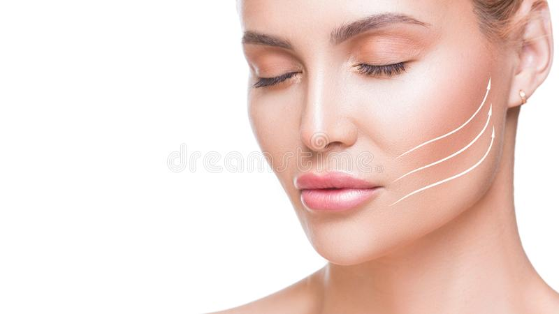 Portrait of attractive woman with arrows on her face over white background. Face lifting concept. Plastic surgery stock image
