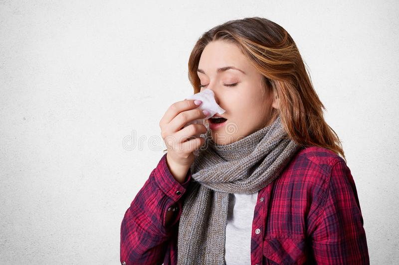 Portrait of attractive woman caught cold, blows nose in tissue, suffers from cold, has running nose, being upset as spends time in royalty free stock images