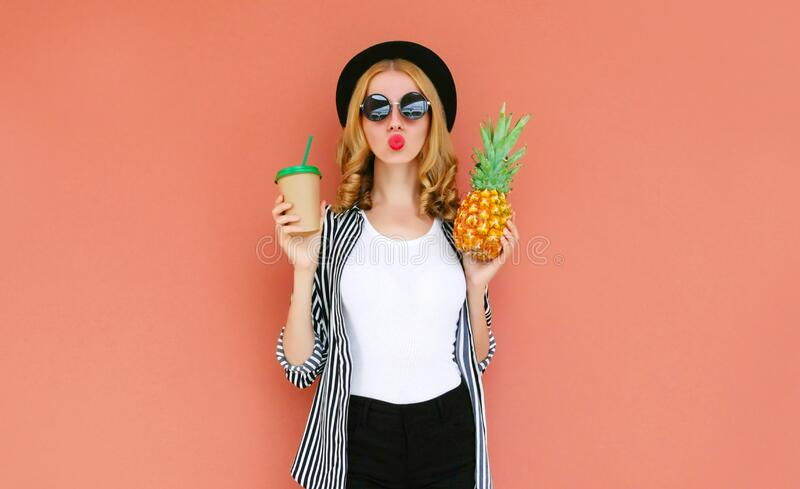 Portrait of attractive woman with cup of juice, pineapple blowing red lips sending air kiss wearing a black hat, sunglasses royalty free stock photo