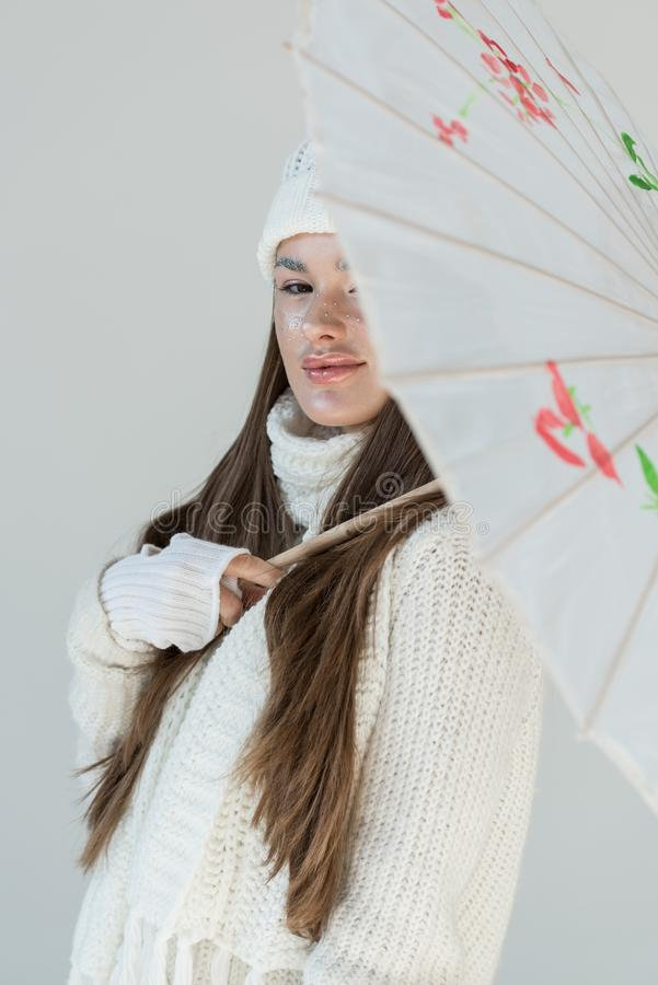 portrait of attractive woman in fashionable winter sweater and scarf standing with japanese umbrella isolated royalty free stock photography