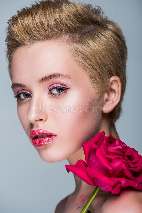 Portrait of attractive woman with glitter on lips and red rose. Isolated on grey stock images