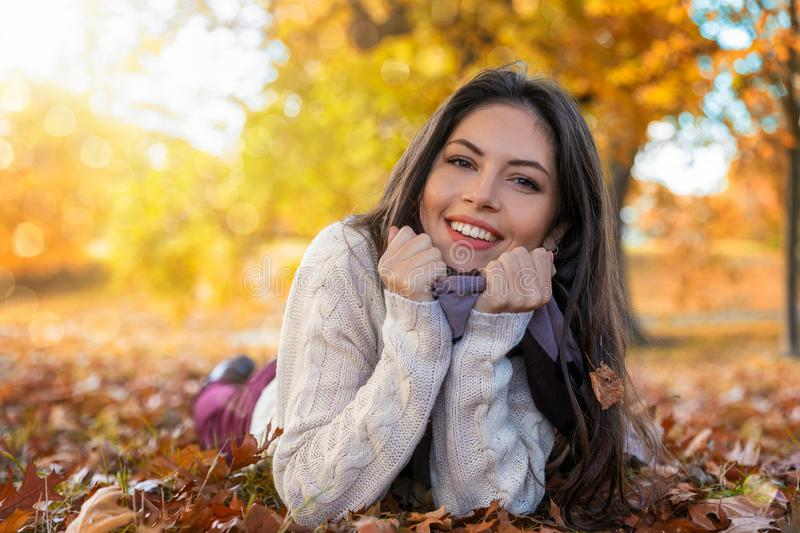 Portrait of a woman lying in autumn leaves in a park. Portrait of an attractive woman lying in colorful autumn leaves in a park during the golden season in royalty free stock photo