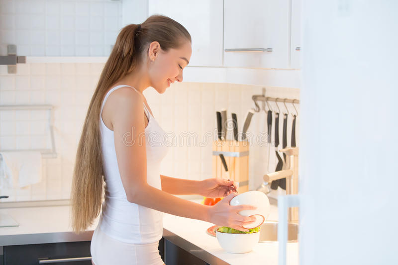 Portrait of an attractive woman making salad on the kitchen. Portrait of an attractive woman making fresh salad on the kitchen stock images