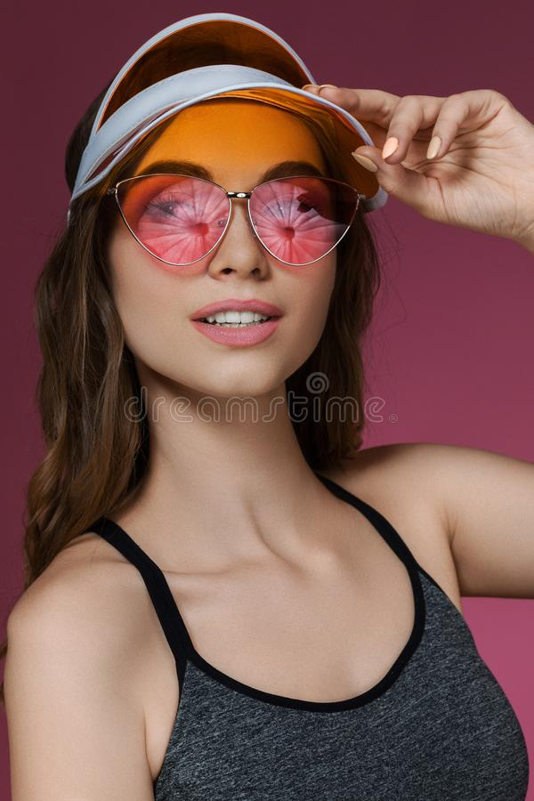 Portrait of attractive woman in orange sun visor and sunglasses. Posing on pink background. girl looking at camera. summer time royalty free stock photo