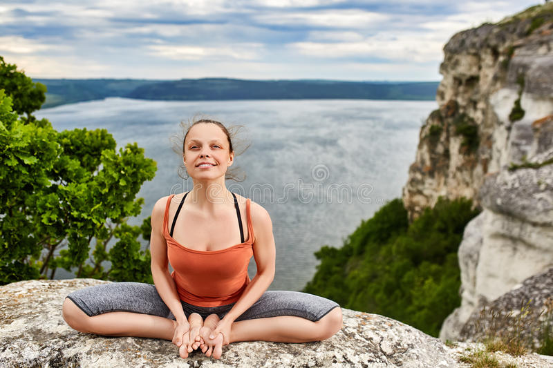 Portrait of the attractive woman is practicing yoga on the rock above river. stock image
