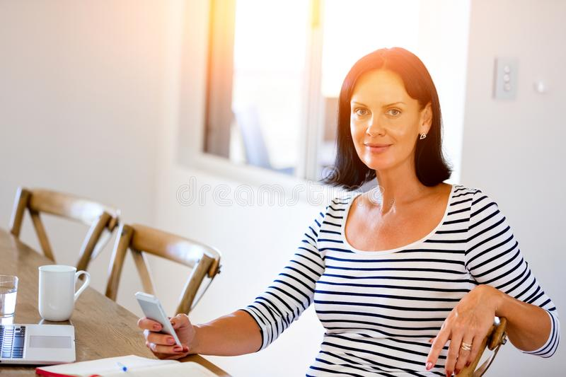 Portrait of attractive woman holding phone stock images