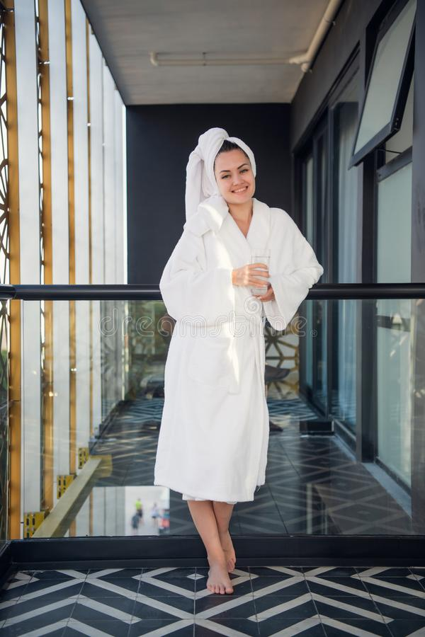 Portrait of attractive woman in soft white bathrobe holding glass of water. She is looking at camera and smiling. Spa royalty free stock photography