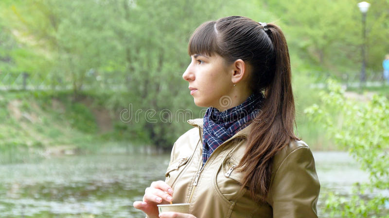Portrait of attractive woman thoughtfully looks out over river a royalty free stock photo