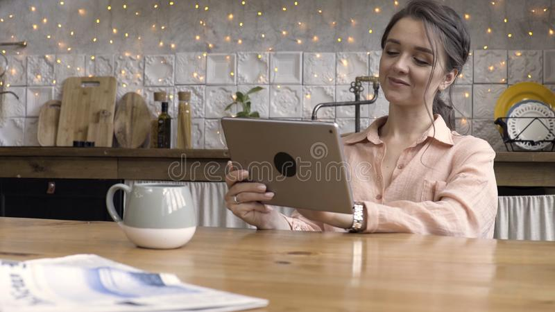 Portrait of an attractive woman using her touchpad and reading something while sitting in the kitchen against decorated stock image