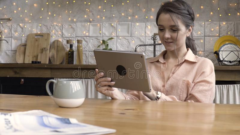 Portrait of an attractive woman using her touchpad and reading something while sitting in the kitchen against decorated stock photography