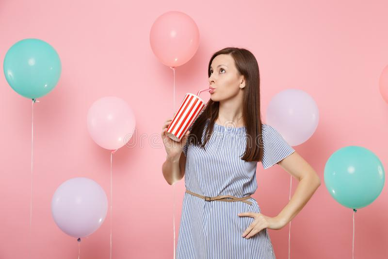 Portrait of attractive woman wearing blue dress drinking cola or soda from plastic cup on pastel pink background with. Colorful air balloons. Birthday holiday royalty free stock photos
