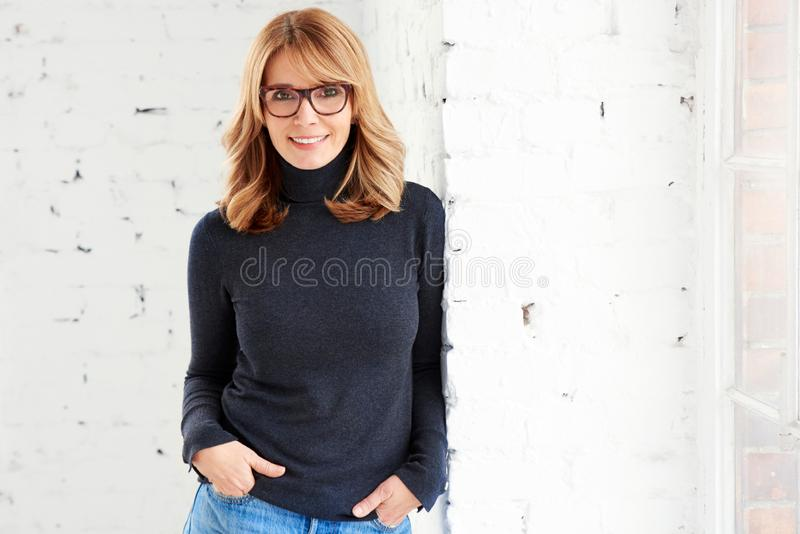 Portrait of attractive woman wearing roll neck sweater and jeans while looking at camera and smiling stock photo