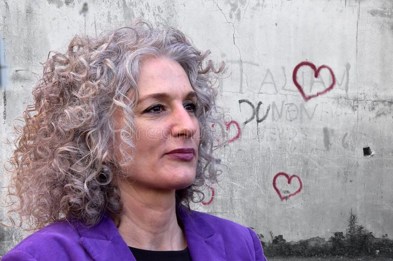 Woman with wonderful hair in front of a wall with graffiti hearts stock photos